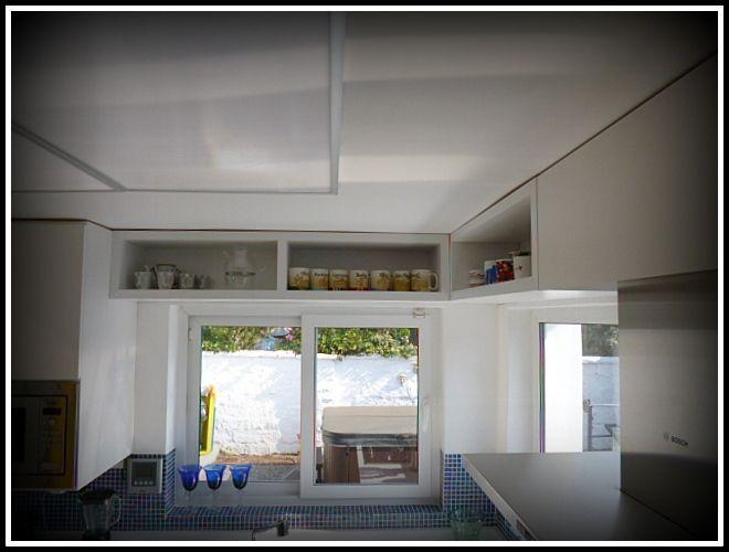Cocina enchapada con cubiertas voladizas para ocupar el máximo espacio.