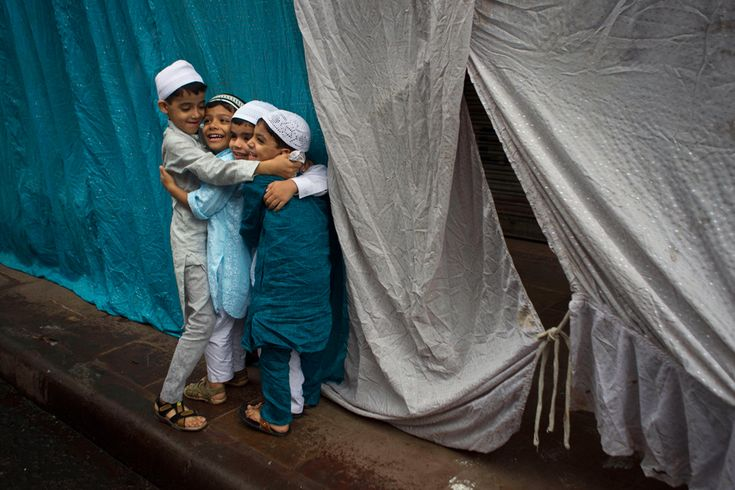 Muslim children hug after offering Eid prayers in New Delhi. Eid al-Fitr marks the end of the holy month of Ramadan, during which Muslims all over the world fast from sunrise to sunset. (AP Photo/Tsering Topgyal).