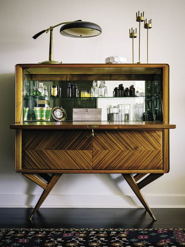Place a mirror and some glass shelves inside a vintage cabinet for a nice bar