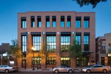 """Vertical elements and orange brick on the Old Town School's new East Building evoke the façade of the client's headquarters across the street, which was created through adaptive reuse of an Art Deco library. Precast concrete panels interpret the word """"music"""" in ancient and modern languages."""