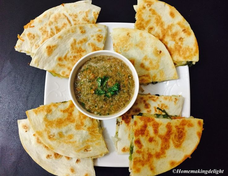 Veg Quesadilla is a (flour) tortilla sandwich stuffed with veggies & cheese and cooked on a hot pan, usually served with sour cream or salsa.