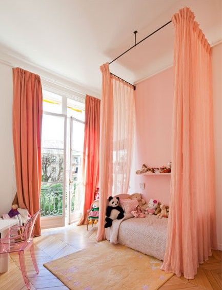 Even if you do not have high ceilings like this putting curtains close to ceiling give the illusion of taller ceilings.  Also love how the curtains around the bed coordinate with windows and provide a cozy little area for any princess to sleep