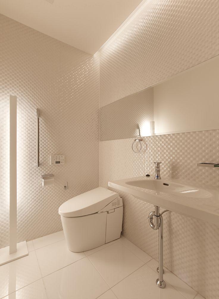 非日常と清潔感をテーマにトイレを店舗のリフォーム。天井際のライン照明、手すり脇のスタンド照明と、間接照明を巧みに仕込んで落ち着きと広がりを生み出しました。スッキリとした白い空間が証明によってタイルの通夜質感が際立ちます。