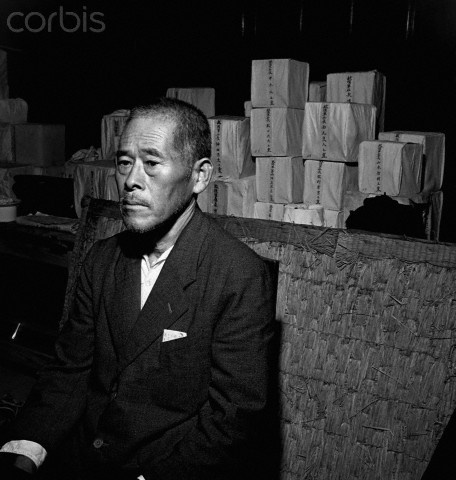 A Japanese man sits in a Buddhist temple in front of ceremonial boxes containing the ashes of cremated victims of the Hiroshima blast. September 1945.