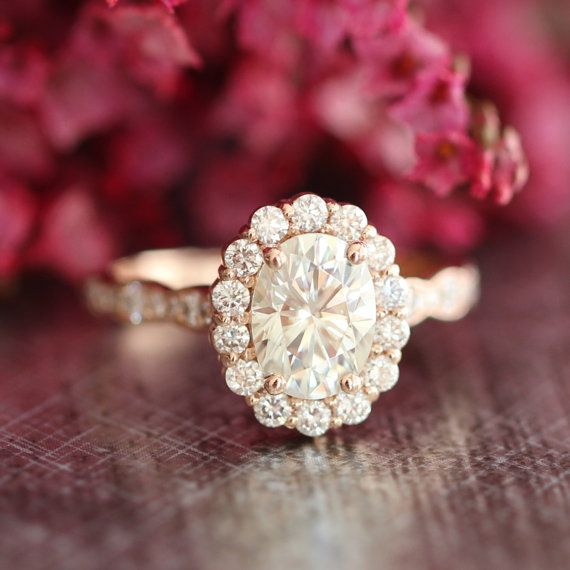This vintage inspired halo diamond moissanite engagement ring features a 8x6mm oval cut forever briallint moissanite set in a solid 14k rose gold