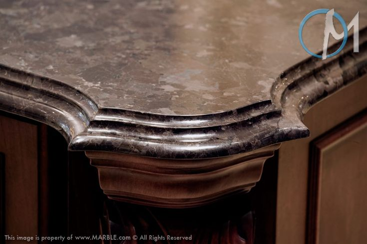 The cove ogee edge is complimented by a sleek Platinum Bahia stone and ornate cabinetry design.