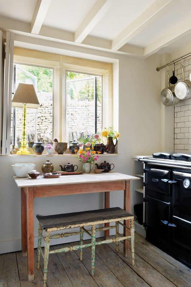 Caroline+and+Fatimah's+collection+of+pottery+bowls+and+jugs+is+displayed+along+the+stone+window+sill+next+to+a+Rayburn+cooker+in+the+kitchen.