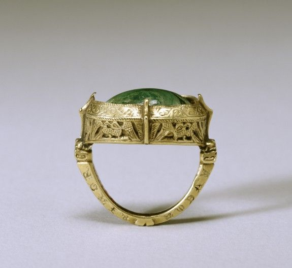 """This elaborate bishop's ring has the typical combination of a gold setting with a single, large stone, in this case malachite. The gold is decorated with openwork eagles, animal heads, and floral elements. The malachite is probably meant to resemble """"toadstone,"""" a green stone said to be found on the head of a toad and believed to have healing qualities. These rings had to be large as bishops normally wore them over gloves on the third finger of the right hand. English, 13th century"""