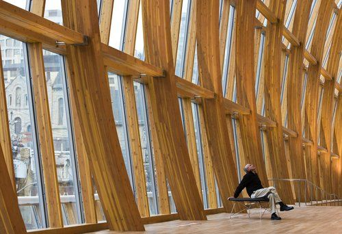 A person surveys the wooden structure in the newly renovated and redesigned Art Gallery of Ontario in Toronto, which was designed by architect Frank Gehry.