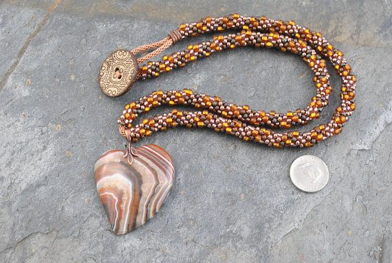 Druzy Agate Heart Pendant Necklace with Kumihimo Bead Strand #heart #heartpendant #pendantbead #pendantbeadnecklace #necklace #kumihimo #kumihimonecklace #artisan #artisannecklace #woven #knotted #handmade #handwoven #handknotted #oneofakind #boho #bohemian #druzy #agate #druzyagate #striped #miyuki #seedbeads #miyukiseedbeads #metallic #matte #iridescent #copper #bronze #pink #unique #flexible #lightweight #japanese #weaving #japaneseweaving