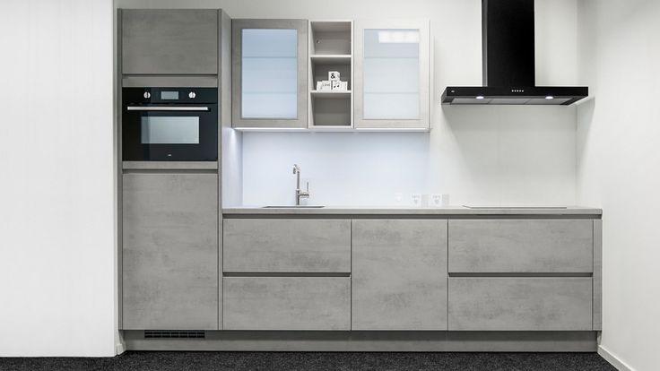 Keukenloods.nl - Strakke rechte keuken in de kleur betongrijs. De keuken is voorzien van ETNA apparatuur. Een opvallend element in de keuken is de zwarte afzuigkap. Deze keuken is te zien in de vestiging Veendam.