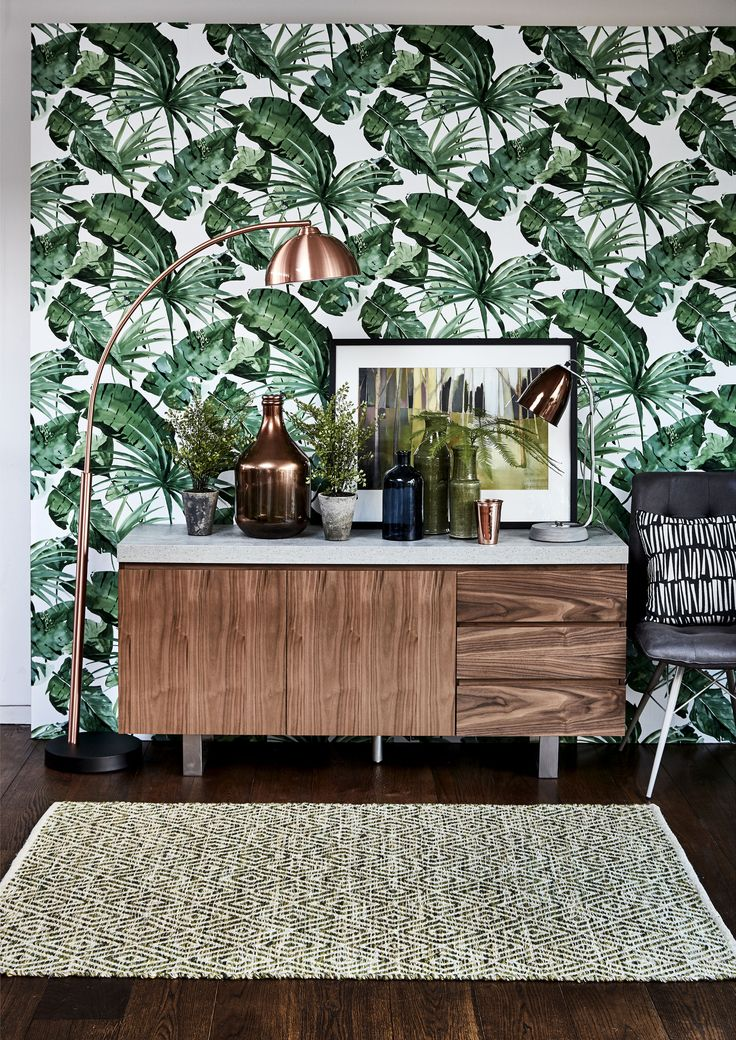We love tropical interiors right now. Get the look with a bold leaf-print wallpaper and complete the look with retro-inspired wood furniture and copper accessories for a vibrant finish. #interiorinspiration #homedecor