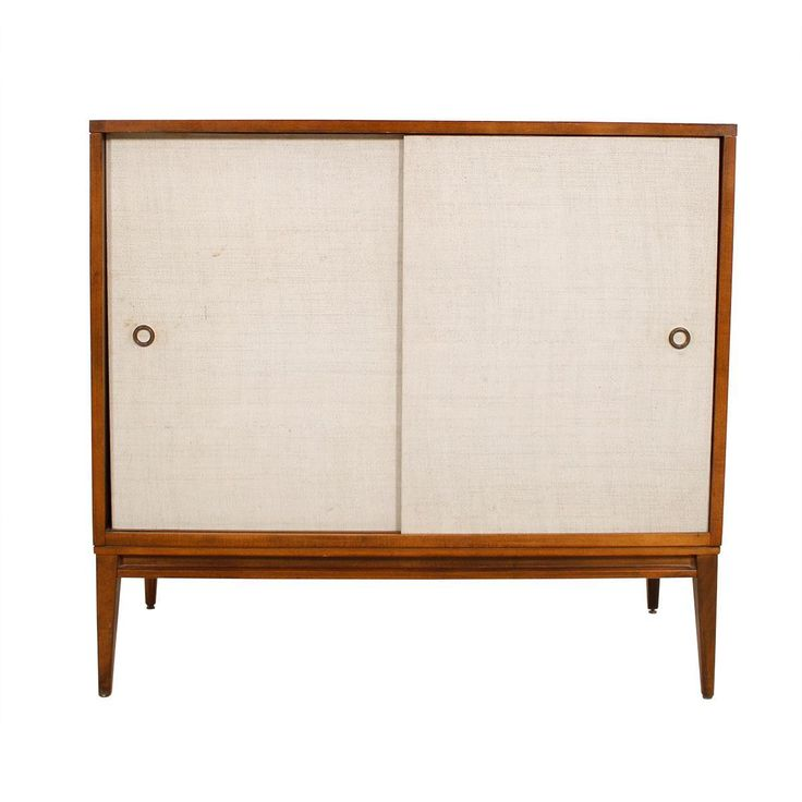 This Paul McCobb Planner Group Compact Cabinet for Winchendon Furniture dates to the 1950s. It's constructed of solid maple stained walnut that complements the creamy grasscloth sliding doors.  Inside is an adjustable shelf making this a great piece for media storage or use as a bar cabinet.  Small circular brass handles on each door, the shape of the legs and the details on the base add to the piece's overall refined design.