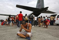 A survivor from Tacloban, which was devastated by Typhoon Haiyan, sits on the ground after disembarking a Philippine Air Force C-130 aircraf...