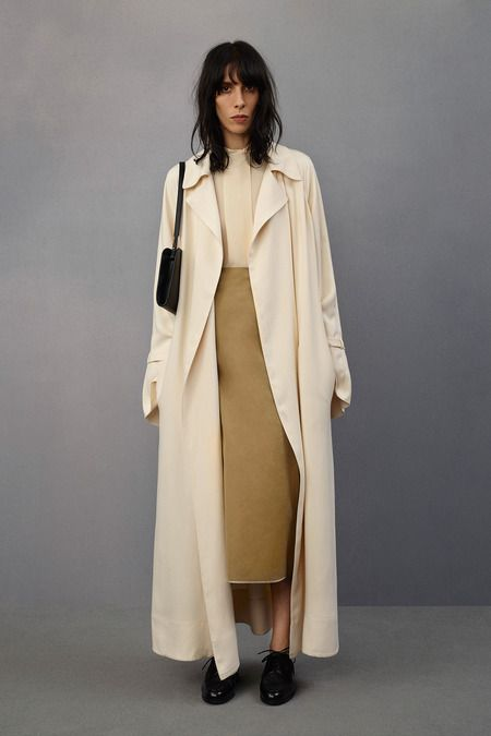 The Row Resort, beige coat, beige silk top, yellow skirt, black pouch, black shoes