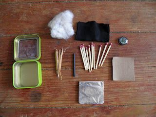 A fire starting kit includes mint tin, matches, tinder, char cloth, cotton, aluminium foil, sandpaper, fire steel