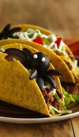 Who says Halloween food has to be sweet? These tasty tacos are hiding a spooky surprise: a giant spider made from olives and sour cream. Simply arrange them to peek out of the shells. It's a trick and a treat!