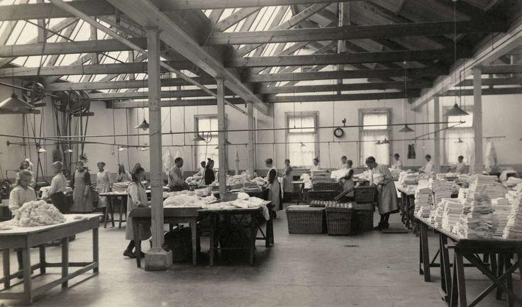 In een opgeruimde ruimte zijn voornamelijk vrouwen aan het werk op een vouw - en mangelafdeling van een wasserij. Op een schragentafel liggen hoge stapels opgevouwen wasgoed. De ruimte is goed verlicht door ramen en een glazen plafond. Arnhem, 1922.