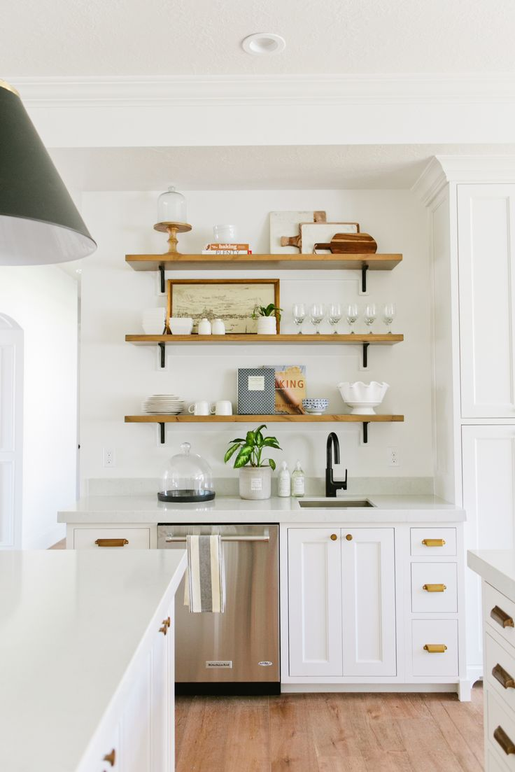 White kitchen cabinets brass pulls floating wood shelves Open shelving