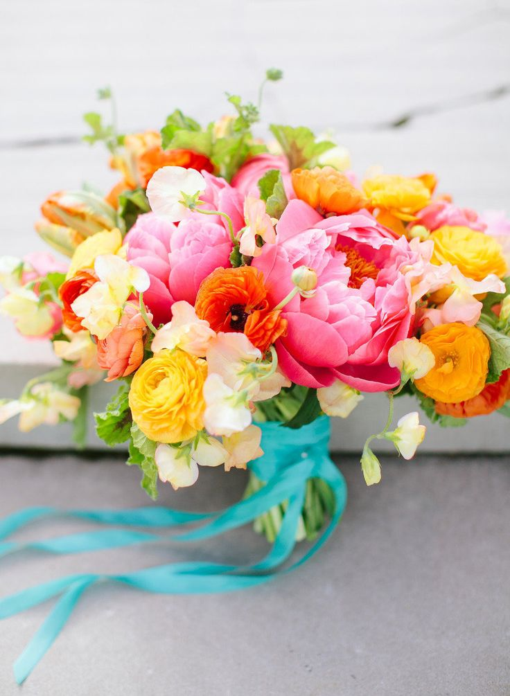coral peonies orange and yellow ranunculus and sweet peas with green foliage and turquoise ribbon