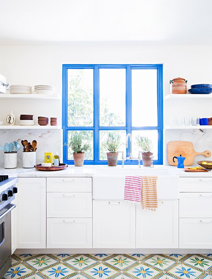 Une cuisine immaculée, fenêtre bleu électrique et carreaux de ciment à motif fleuri