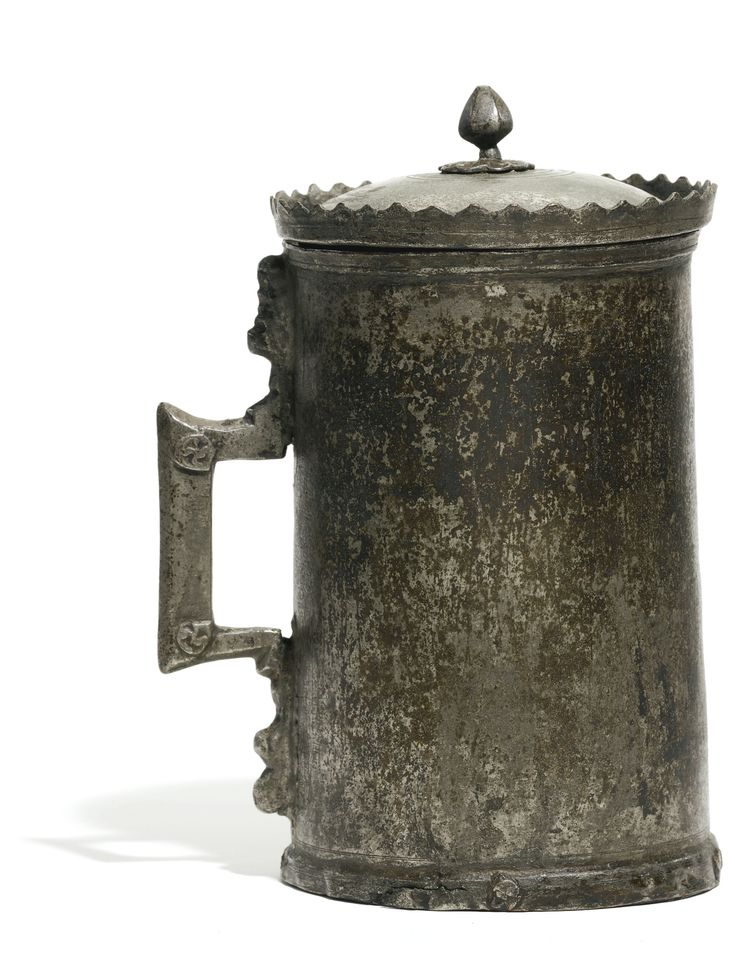 A RARE OTTOMAN TINNED-COPPER TANKARD, TURKEY, 16TH CENTURY the cylindrical body with a squared handle decorated with four foliate medallions and a slightly domed cover with finial and crowned rim, rosette worked in relief to underside