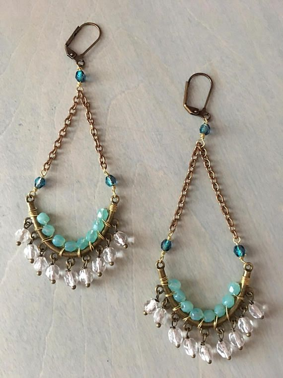 21/2 inches in Length these lovely chandler. Woven sea foam beads wrap around the curve while crystal clear beads dangle from the bottom.