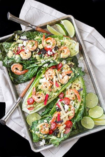 Southwestern Inspired Grilled Romaine Salad has a delicious smokey flavor topped with grilled shrimp and corn and dressed with avocado cilantro lime sauce!