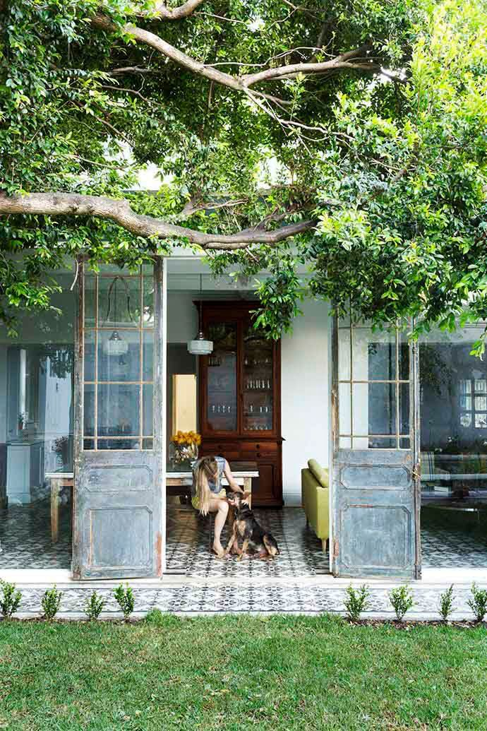 Vintage metal French doors leads to an outdoor tile patio by the dining room on Thou Swell @thouswellblog