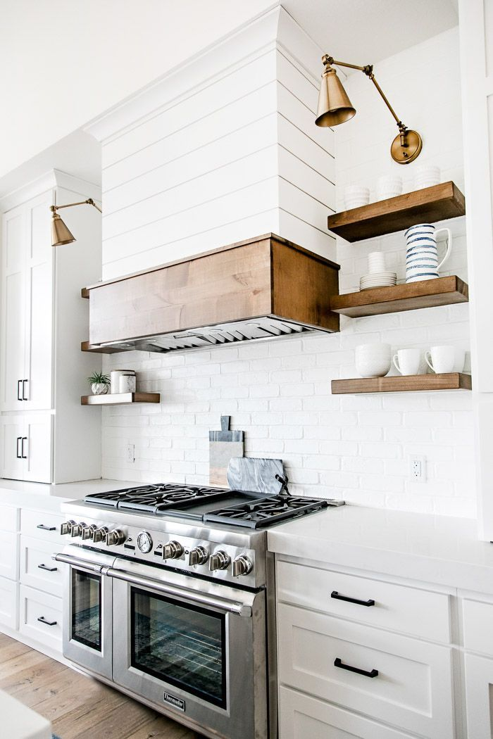 White modern farmhouse kitchen with shiplap range hood, open wood shelving, and swing arm sconces