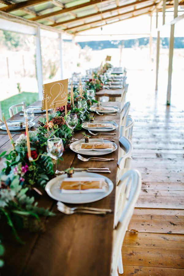 Long wood farm tables, greenery, candle sticks | Image by Green Antlers Photography