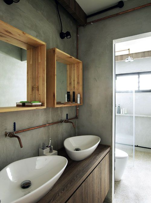 The exposed copper of the pipes and the wood-framed mirrors give a raw and natural feel to this bathroom.
