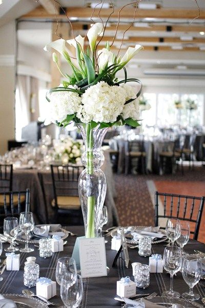Other tables will feature a tall silver vase filled with cream hydrangeas, folded green ti leaves, and white calla lilies surrounded by silver mercury glass LED votives.
