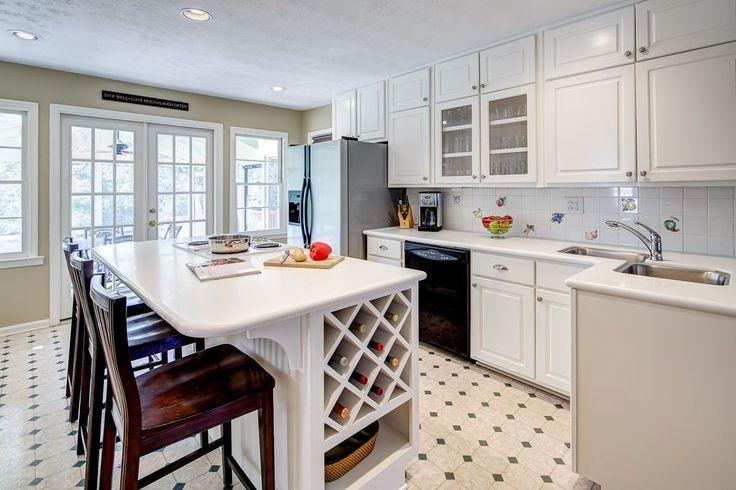 Weiße Kacheln mit gräulichen Achteck Punktmuster erstellen visuelle Interesse in dieser weißen gewaschenen L-förmige Küche mit einer zentralen Kücheninsel.