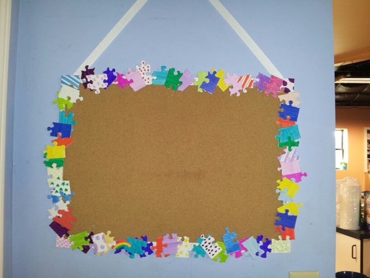plain cork bulletin board and white puzzle pieces markers and a hot glue gun