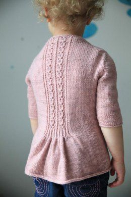 This little cardigan is worked from the top. You finish the cardigan with an I Cord Bind Off at the bottom, on the neck and along the fronts. It is worked with a negative ease. If you want to wear a sweater underneath you must choose a bigger size. The sample shown is knit in Lilou, MCN in Rose Poudré. Debbie Bliss, Rialto 4 Ply in Blush is a suitable substitute yarn.
