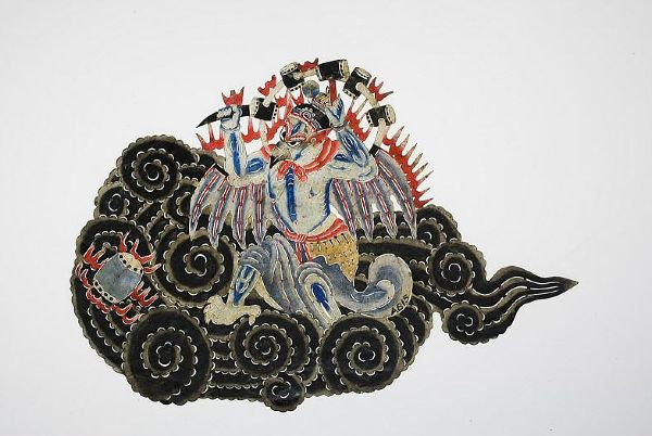 Chinese shadow puppet: Thunder god using his hammer and chisel...