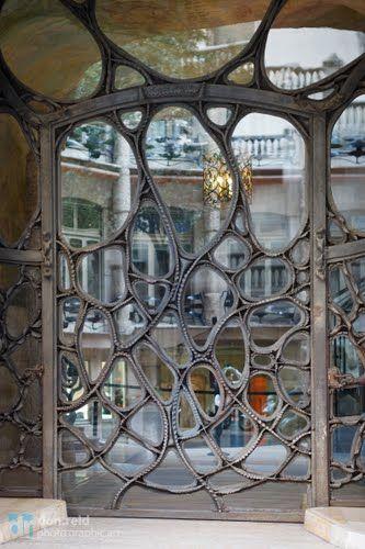 Las dos puertas de entrada están realizadas en hierro forjado y vidrio, de tal forma que actúan a la vez como puerta y como verja de seguridad. Su diseño es orgánico, con una serie de estructuras de diversa forma que pueden recordar diversos diseños elaborados por la naturaleza, como caparazones de tortuga, alas de mariposa o tejidos celulares.  Su estructura amplia y diáfana permite el paso de la luz con facilidad, e ilumina con profusión los vestíbulos interiores.