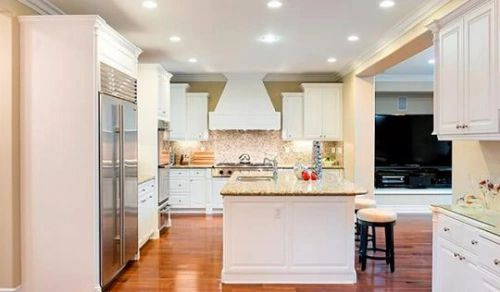 Solid mix of textures and lighting.  Stair stepped cabinetry next to hooded range, crown molding, backsplash, stainless steel appliances, double door fridge, double ovens, island sink, ease of movement and light color palette make this a personal favorite.