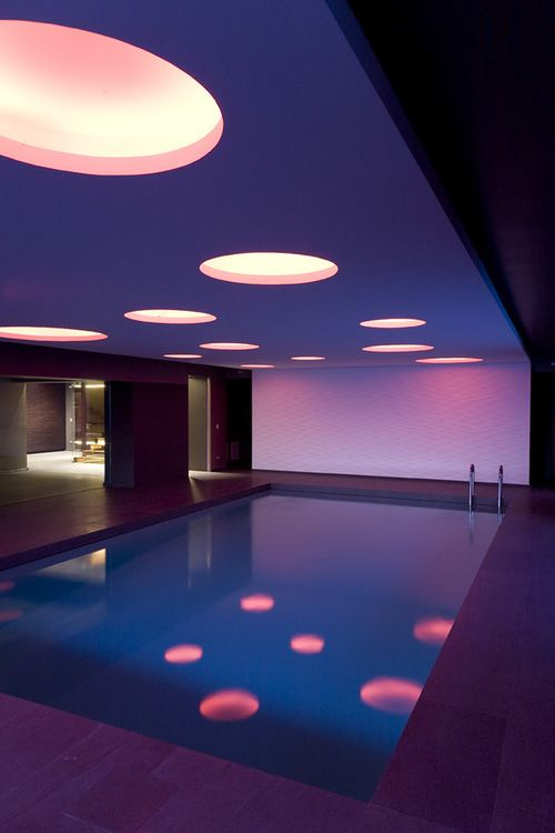 Indoor Pool with large overhead lights and accent lighting.