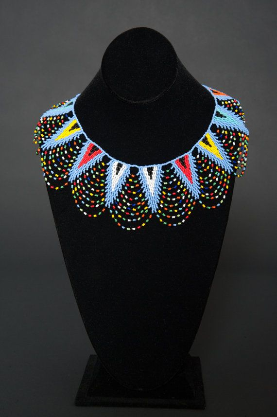 Lavender blue / Multi-colors  Lace necklace with a beaded ball and loop closure. Necklace measures approximately 12.2 inches (18.5 inches including loop and beaded ball closure). Hand beaded by young Zulu women from Durban, South Africa.  *While all efforts are made to show the jewelry as accurately as possible, dimensions and colors may vary slightly.
