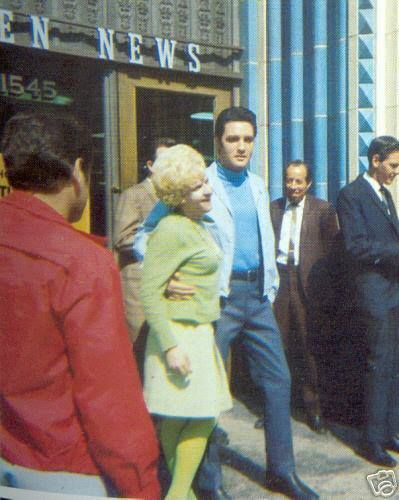 "Ohhh, she is lucky green woman!/ ""@Bri Allard Taken on the set of ""Live a Little, Love a Little"" in front of the CITIZEN NEWS, 1968. Actually it's NOT a woman but a man in green! :-D It was just a joke. Elvis didn't know about it. By the way, the man in the red jacket with his back to the camera is Charlie Hodge."" Tanja Graf' quote. Tks"