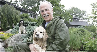 Boston Channel 7 news anchor Randy Price poses with his cocker spaniels Annie (left) and Grace at his home in Kittery Point, Maine.