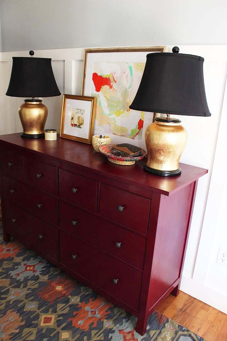Berry dresser with colorful kilim rug  gold lamps  and board and batten walls  entry
