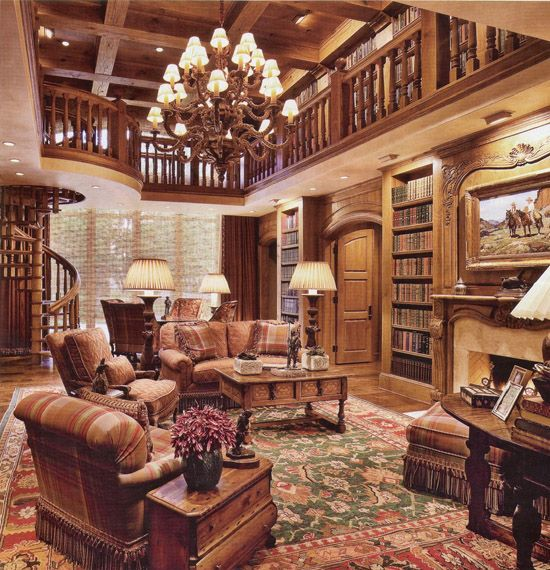 """The two-story library at oil billionaire T. Boone Pickens' guest house on his 68,000-acre Texas ranch. This library has a distinct Western character to it, as might be expected, yet the room is elegant and classic as well. Frank Tenney Johnson's """"Wyoming Cattlemen"""" hangs over the fireplace. A beautiful and warm space for reading."""