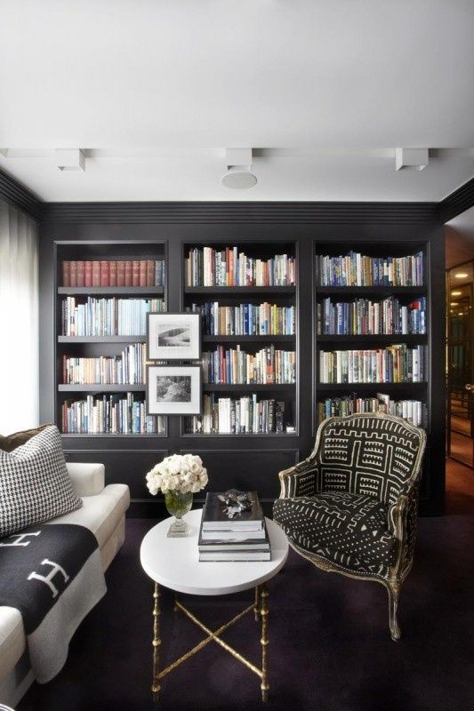 black built-ins, bookcase, black and cream patterned chair, hermes throw, stone coffee table with gold legs