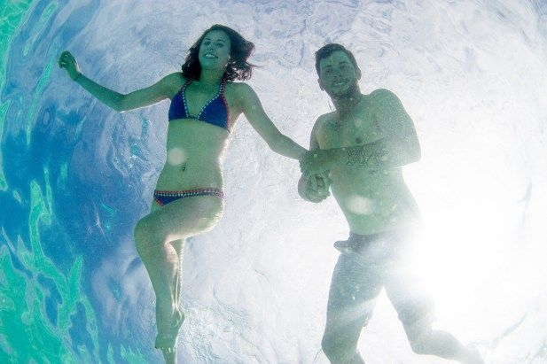 underwater couple in clear Fiji water at Cloud 9 by Anais Photography