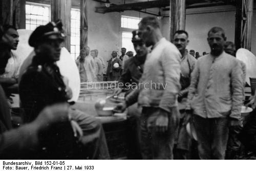 Mealtime at Dachau.  This picture is probably not a candid shot.  On the rare occasions outsiders were allowed into the camps to take photos for propaganda purposes, prisoners and guards were on their best behavior.  Occasionally, the Nazis published pictures of life in the camps to show how happy the prisoners were and how well they were treated.