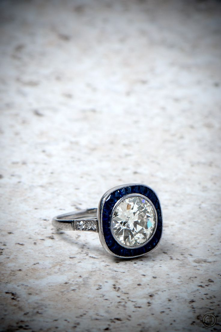 An epic estate diamond engagement ring, surrounded by a stunning row of sapphires, and set in handmade platinum.