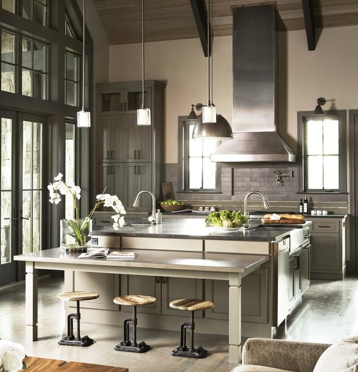 A sophisticated country kitchen with clean, modern lines designed by Linda McDougald of Postcard from Paris Home. The open kitchen features an earthy palette of muted grays and browns, natural accents, warm wooden tones, but sophisticated finishes like stainless steel appliances and sleek range hood. French doors open to screened porch with stone fireplace.